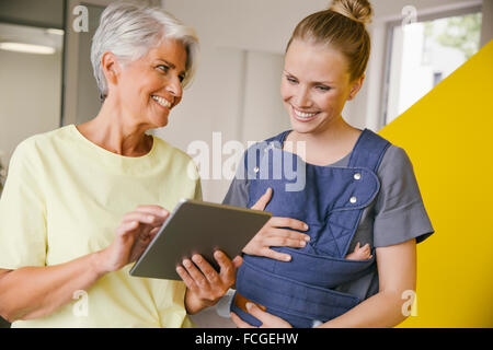 Young mother   baby carrier talking to mature woman   digital tablet in office hallway - Stock Image