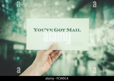 Female hand delivering a postage envelope on blurred urban background. Image has vintage filter applied - Stock Image