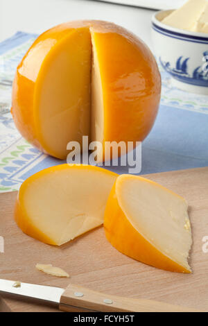 Whole yellow round Edam cheese with slices on a cutting board - Stock Image