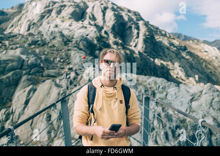 Young Man With Smartphone Standing On Suspended Bridge - Stock Image