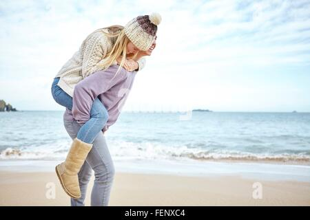 Young man giving girlfriend a piggyback on beach, Constantine Bay, Cornwall, UK - Stock-Bilder