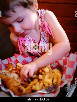 Cute Girl Having Chicken Fingers At Restaurant - Stock-Bilder