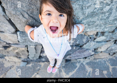 Portrait of little girl with mouth open in front of a rock face - Stock Image