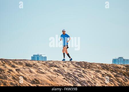 Low angle view of mid adult man running on sand dune, Dubai, United Arab Emirates - Stock Image