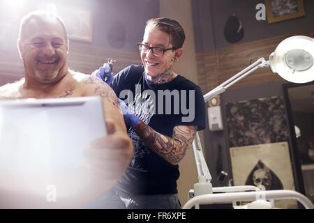 Smiling man with digital tablet getting shoulder tattoo - Stock-Bilder