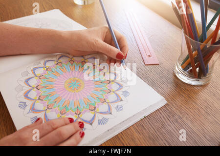 Close up image of woman hands drawing in adult colouring book on a table at home. - Stock-Bilder