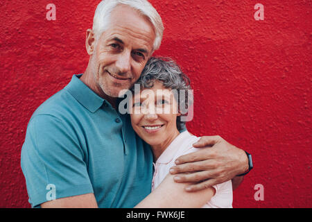 Portrait of loving middle aged couple embracing against red background. Mature man and woman together against red - Stock Image