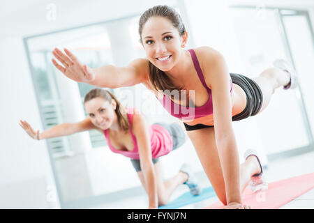 Sporty young women at the gym doing pilates workout on a mat, fitness and healthy lifestyle concept - Stock-Bilder