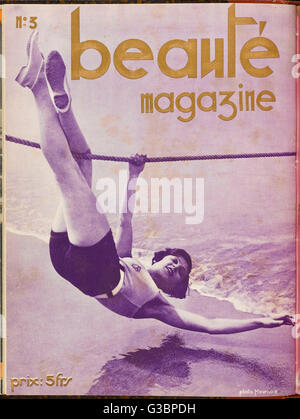 A sporty young lady in shorts  hangs upside down from a rope  above the sea, presumably to  demonstrate her athletic - Stock Image