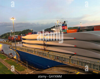 Large cargo ship carrying wind turbine arms going through the Miraflores Locks of the Panama Canal. - Stock Image