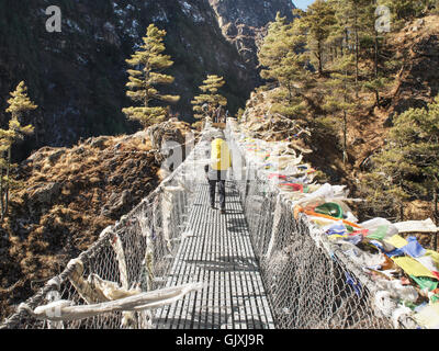 A hiker crosses a suspended bridge in Nepal's Everest Base Camp - Stock-Bilder