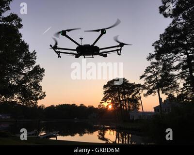 DJI Matrice 600 flying over a lake at dusk in Virginia Beach, VA - Stock Image