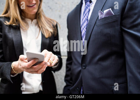 Midsection of businessman and businesswoman standing with smart phone - Stock-Bilder
