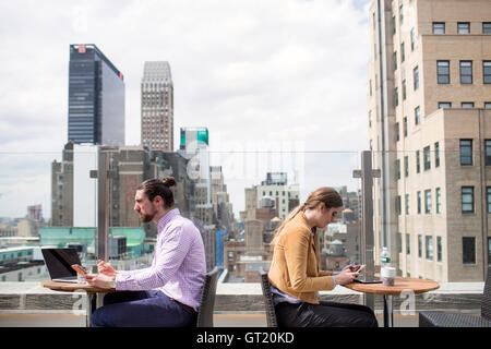 Side view of business people working while sitting at rooftop restaurant by window - Stock-Bilder