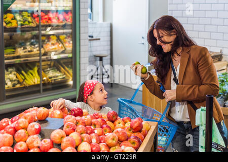 Happy mother and daughter shopping fruits in supermarket - Stock-Bilder