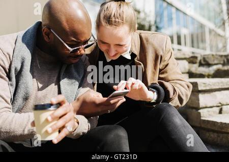 Smiling friends using smart phone on sunny day - Stock-Bilder