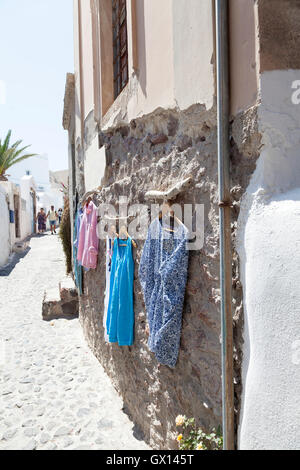 Clothes hanging outside a shop in Santorini, one of the most romantic of the Greek islands. - Stock Image