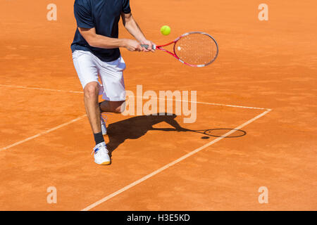 Male tennis player in action on the clay court on a sunny day - Stock-Bilder