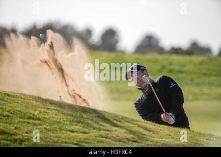 Scotland's Marc Warren plays from the green side bunker at the 14th hole during day three of the Alfred Dunhill - Stock Image