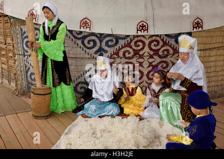 Family in traditional Kazakh clothes working wool into felt and yarn next ot a yurt at Huns Village - Stock Image