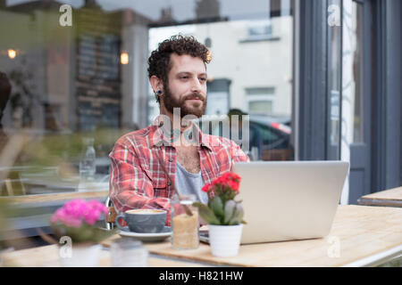 Young tattooed hipster using laptop outside cafe - Stock-Bilder
