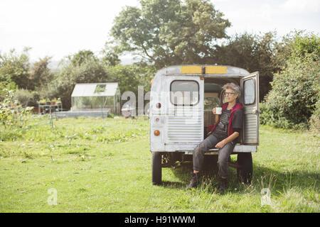 Elderly car mechanic having a tea break - Stock-Bilder