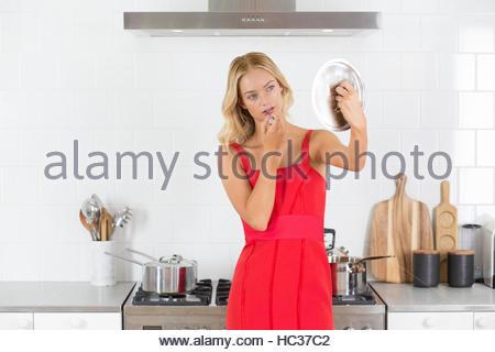 Young woman using saucepan as mirror, applying lipstick - Stock Image
