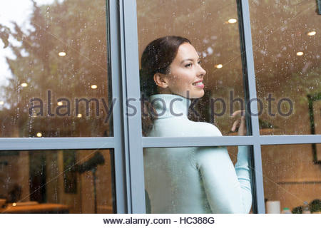 Mid adult woman standing at window. - Stock-Bilder