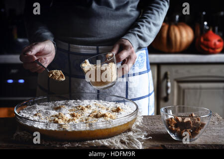 Adding grated crackers in the dough for pumpkin dump cake - Stock Image