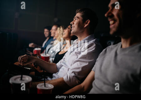 Group of young people sitting in cinema hall watching movie. Multiracial group of friends watching movie in theater. - Stock Image