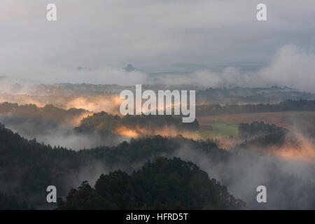 Interesting light, fog and cloud over Saxon Switzerland National Park, Saxony, Germany - Stock Image