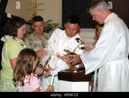 050711-N-5783F-002 Pearl Harbor, Hawaii (July 11, 2005)- Lt. Cmdr. Chris Buziak holds his son during a baptism ceremony - Stock Image