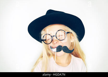 Studio shot of little girl in black hat and glasses holding fake moustache on stick and laughing. - Stock Image