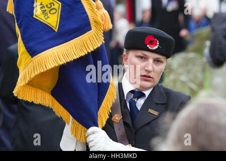 Young woman flag bearer at a British Legion Remembrance Day Parade - Stock Image