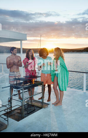 Young adult friends barbecuing, hanging out and drinking on summer houseboat at sunset - Stock-Bilder