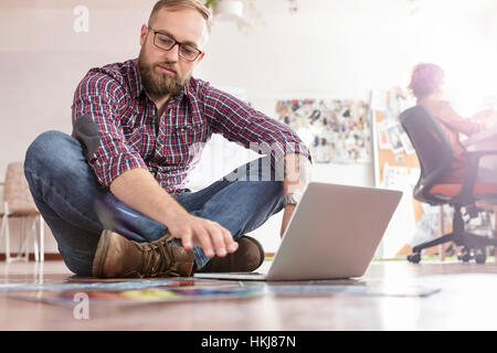 Male design professional reviewing proofs at laptop on office floor - Stock-Bilder