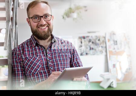 Portrait smiling male design professional using digital tablet in office - Stock-Bilder