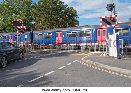 Railway train crossing road with level crossing and bicycle and car waiting - Stock-Bilder