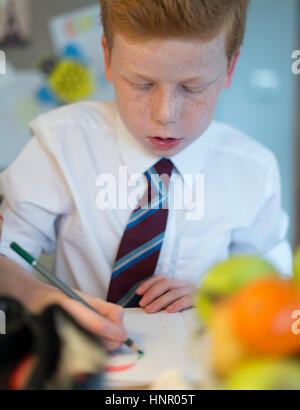 A boy drawing for homework in his kitchen at home. - Stock Image