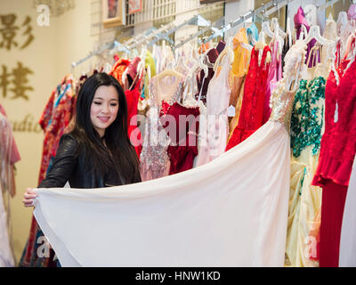 Smiling Chinese woman shopping for dress - Stock-Bilder