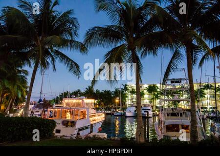 Key Largo Florida Upper Florida Keys Courtyard Key Largo waterfront canal marina yachts boat slip palm tree dusk - Stock Image