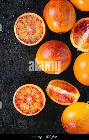 Sliced and whole ripe juicy Sicilian Blood oranges fruits on black wet metal texture background. Top view with space - Stock Image