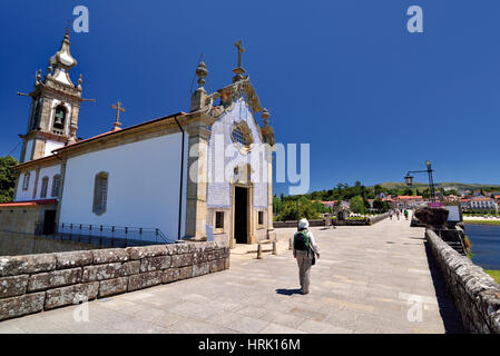 Portugal: Woman with backpack walking along roman bridge and medieval chapel in St. James Way stop Ponte de Lima - Stock Image