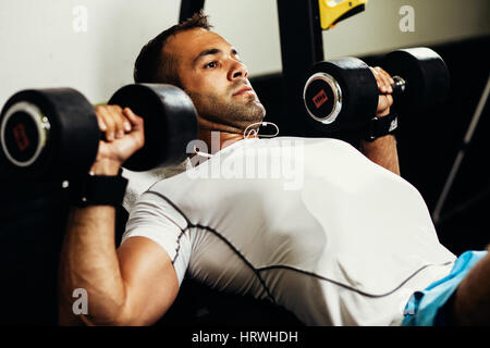 handsome fitness man weightlifting workout in gym - Stock Image
