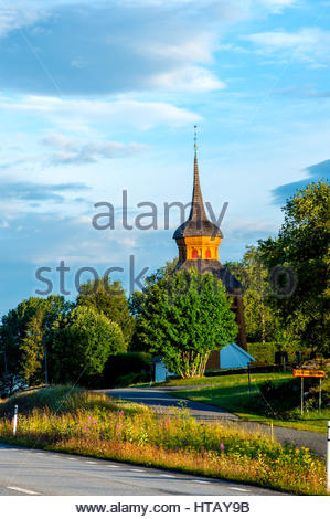 Warm colours of morning sunrise up in the mountains of Sweden. Clock tower with roof of wooden shingles. - Stock Image