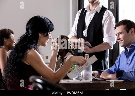 Waiter serving diners in restaurant, waiter using digital tablet - Stock-Bilder
