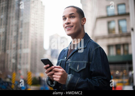 Young man standing in street, using smartphone, Manhattan, New York, USA - Stock-Bilder
