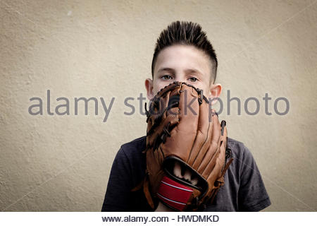 Boy covering mouth with baseball glove - Stock-Bilder