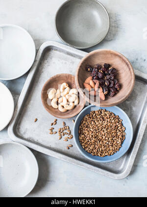 Studio shot, overhead view of cashew nuts, almonds, seeds and dried fruit in bowls - Stock-Bilder