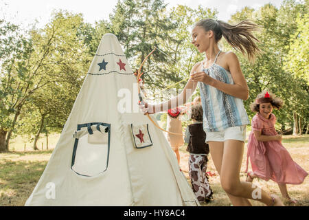 Young children play games outside in the sunshine - Stock Image